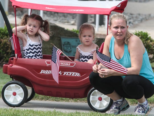 Grace Moebius, 4, prepares for the sirens as her sister Caroline, 4, and mother Katie Moebius, look on during the start of the annual Memorial Day Parade in Morristown.