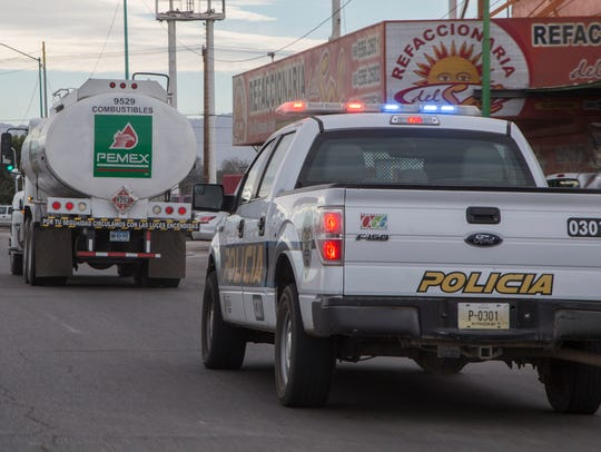 A police vehicle escorts a gasoline delivery truck