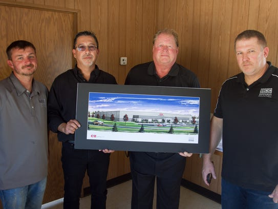Holding an artist's rendering of the new CZ Cartage