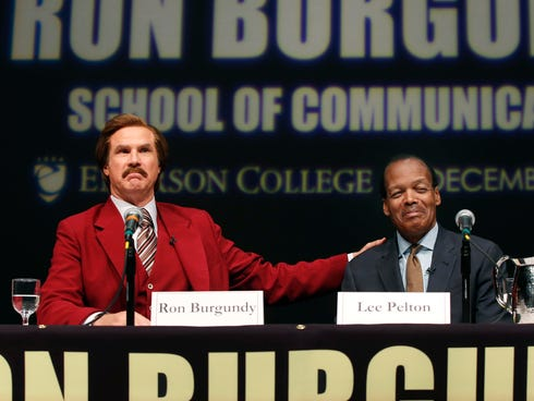 Will Ferrell, left, who plays TV anchorman Ron Burgundy, stays in character and gestures during a news conference at Emerson College in Boston.