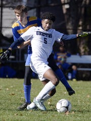 World of Inquiry's Yusuf Jeylani shields the ball from Lansing's Ryan Besemer during Saturday's Class C semifinal. The Griffins won 2-1.