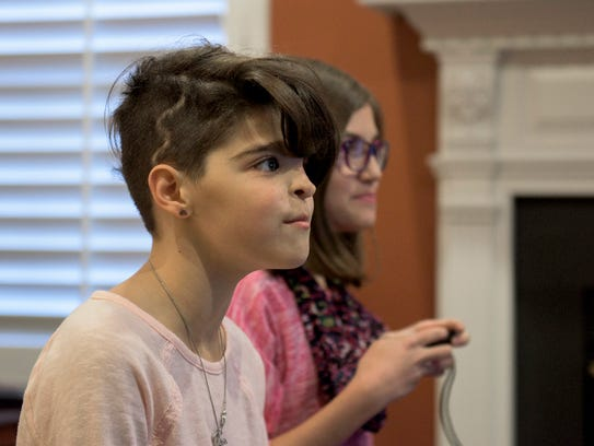 """Maryelena Baldassarre, 11, left, plays video games with her twin sister, Annalisa Baldassarre, at their Sicklerville home. Maryelena opted to show off the lightening bolt-shaped scar on her scalp with a short new haircut. """"It's cool,"""" she says."""