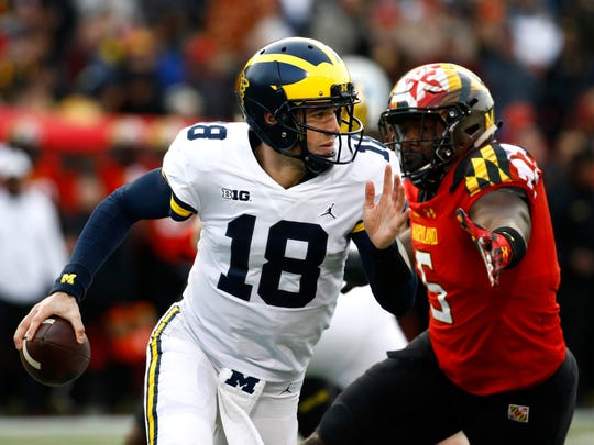 Michigan quarterback Brandon Peters (18) looks for a receiver as he is pressured by Maryland defensive lineman Cavon Walker in the first half on Saturday, Nov. 11, 2017, in College Park, Md.