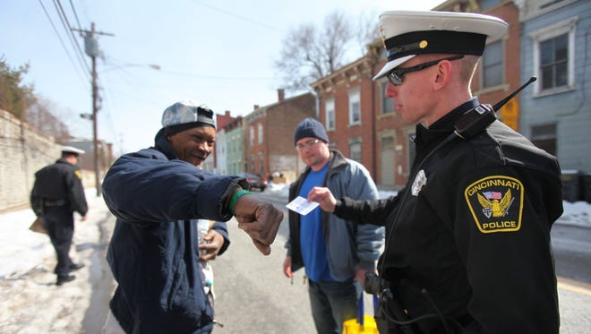 Cincinnati Police Officer James Ball talks with Melvin Mitchell on McMicken Avenue, where newly graduated police officers were handing out bagged lunches in Over-the-Rhine.