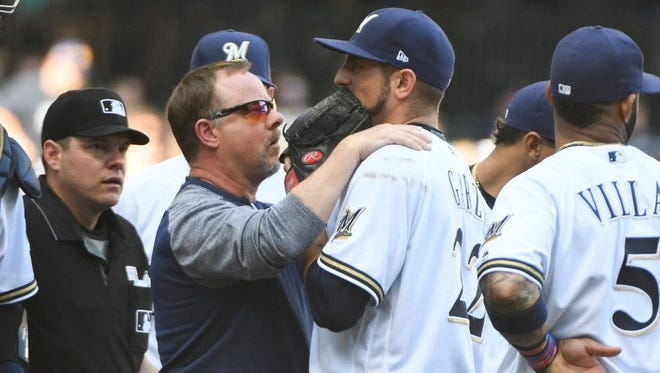 Matt Garza is tended to by Brewers trainer Dan Wright after he collided with first baseman  Jesus Aguilar as they were trying to field a ground ball on Saturday.