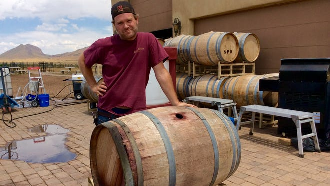 Kief Manning poses next to the barrel of wine that fell on his head, nearly killing him.