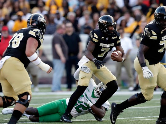 Southern Miss quarterback Kwadra Griggs (7) is tackled by North Texas linebacker E.J. Ejiya (22) as he tries to follow his blockers during the first half of their NCAA college football game Saturday in Hattiesburg.