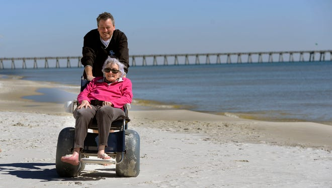Emerald Coast Hospice patient Claudia Rich is is pushed along Pensacola Beach in a special wheelchair by her son Claud Rich Saturday afternoon. Claudia's wish was to spend time at the beach with family. Emerald Coast Hospice paid for rooms at the Holiday Inn Express for her and her family for three days and the use of a special wheelchair so she could have access to the beach.