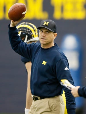 Michigan football coach Jim Harbaugh works with the offense during practice March 19, 2015 in Ann Arbor.
