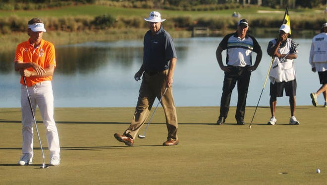 Bernhard Langer, left, and Kirk Triplett, center, look at Langer's missed par putt on the 18th green Sunday during the final round of the ACE Group Classic at The Twin Eagles Club in Naples. Triplett made his par putt and won the tournament.