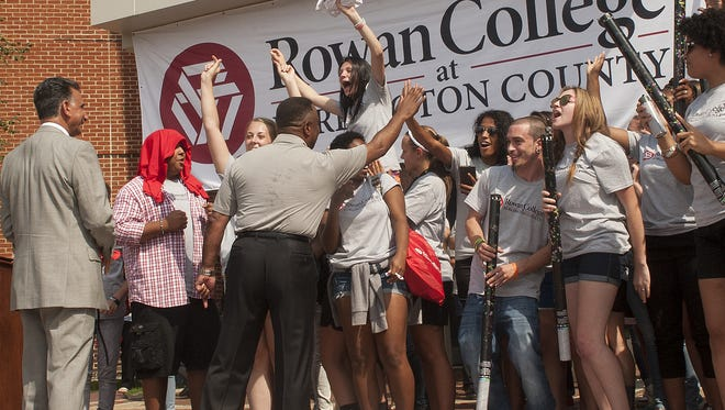 Burlington County College President Paul Drayton Jr. , center, and Rowan University President, Dr. Ali Houshmand, left, interact with students during the unveiling of the new college logo after the  announcement of the partnership between the two educational institutions last summer.