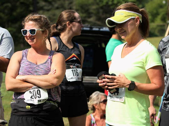 Shawn Fadoir, left, and Charla Greene listen to final words of encouragement from Mindy Bayless before beginning their first trail run in the Gateway 10K.
