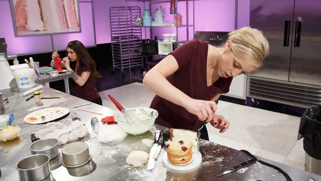 """Contestants Kayla Trahan, right, and Fallon Bearb, left, work on a Captain-America-themed red, white and blueberry cake during the first Captain America challenge, as seen on Food Network's """"Cake Wars."""""""
