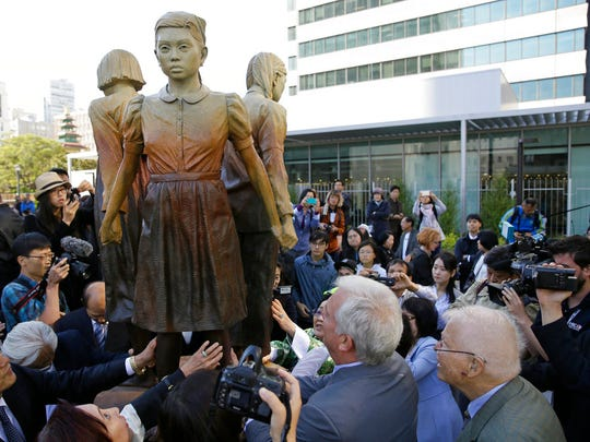 """In this Friday, Sept. 22, 2017, file photo, people move in to take a closer look at the """"Comfort Women"""" monument after it was unveiled in San Francisco. Japan has expressed strong regret over San Francisco's decision to give formal city property status to a statue commemorating women who worked in military-backed brothels for Japanese troops during World War II, with Osaka declaring it will terminate its 60-year sister-city ties."""