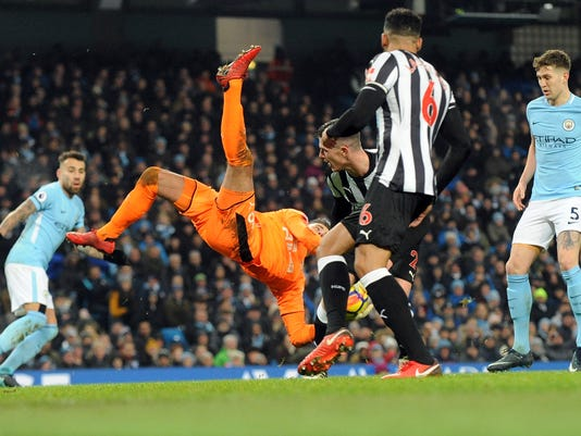 Newcastle goalkeeper Karl Darlow, center left, dives for a save during the English Premier League soccer match between Manchester City and Newcastle United at the Etihad Stadium in Manchester, England, Saturday, Jan. 20, 2018. (AP Photo/Rui Vieira)