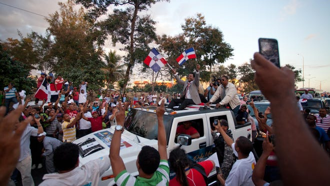 Pedro Martinez greets fans, while holding representations of his country's national flag, as he takes part in a welcome caravan in his honor, in Santo Domingo, Dominican Republic.
