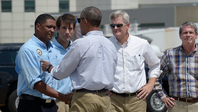 President Obama is greeted by, from left, Rep. Cedric Richmond, D-La., Rep. Garret Graves, R-La., Sen. Bill Cassidy, R-La., and Sen. David Vitter, R-La. after arriving on Air Force One in Baton Rouge Aug. 23, 2016 to tour flood-damaged areas.