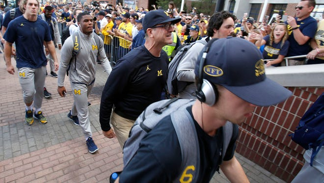 Michigan head football coach Jim Harbaugh heads into Michigan Stadium with his team before the game against MSU in Ann Arbor on Sat., Oct. 7, 2017.