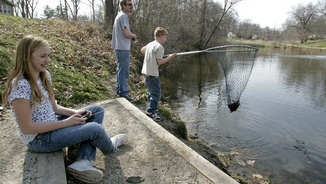 Shelbi Langford, 13, laughs as she maneuvers a radio controlled boat in the pond at Witmer Park in 2008 while her father, Jason, fishes as her brother, Dakota, 6, plays with a fishing net.
