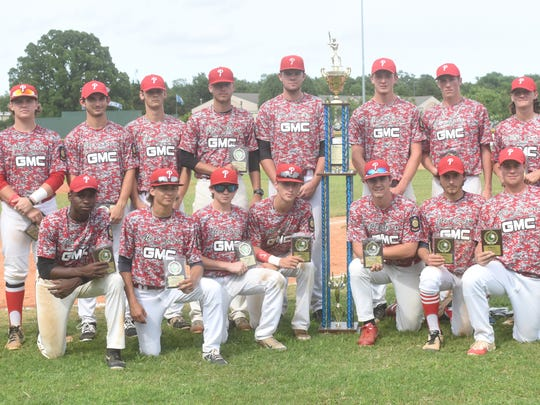Members of the Paragould Glen Sain GMC team pose with the championship trophy of the 31st annual Mickey Huskey Twin Lakes Classic.