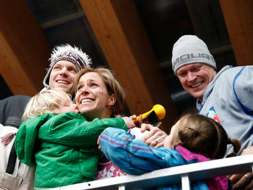 Noelle Pinkus-Pace (USA) after winning the silver medal in the ladies skeleton hugs her family in the spectator area.