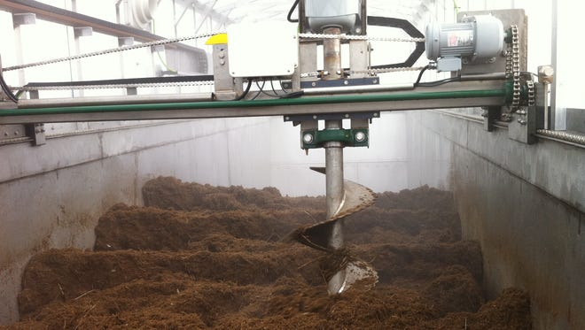Steam rises from material inside Colorado State University's Earth Flow composting system. An auger aerates the material, helping it quickly turn from food scraps and horse bedding into usable compost.