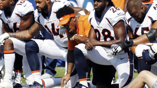Denver Broncos players, including Jamaal Charles (28) kneel during the national anthem prior to Sunday's NFL football game against the Buffalo Bills in Orchard Park, N.Y.