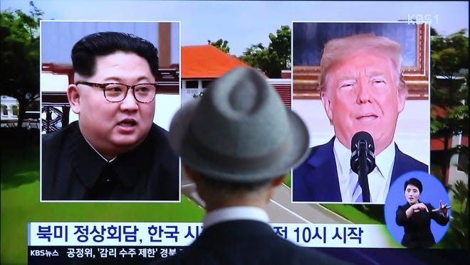 """A man watches a TV screen showing file footage of U.S. President Donald Trump, right, and North Korean leader Kim Jong Un during a news program at the Seoul Railway Station in Seoul, South Korea, Monday, June 11, 2018.  Final preparations are underway in Singapore for Tuesday's historic summit between President Trump and North Korean leader Kim, including a plan for the leaders to kick things off by meeting with only their translators present, a U.S. official said.  The signs read: """" Summit between the United States and North Korea."""""""