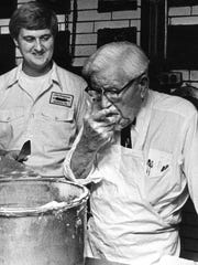 Col. Harland Sanders tastes the icing for his birthday