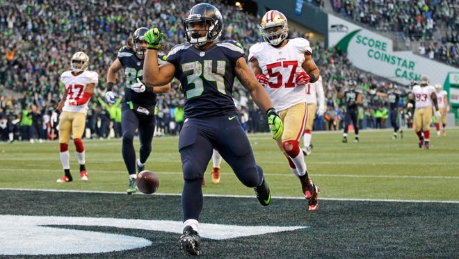 Seattle Seahawks running back Thomas Rawls (34) drops the ball after scoring a touchdown ahead of San Francisco 49ers inside linebacker Michael Wilhoite (57) during the second half of an NFL football game Sunday, Nov. 22, 2015, in Seattle.