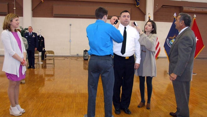 Michigan National Guard soldier, Pablo Estrada, receives the rank of brigadier general from his daughter Natalie and son Christopher while his wife Roberta and brother David look on during a promotion ceremony held April 9 in Detroit.