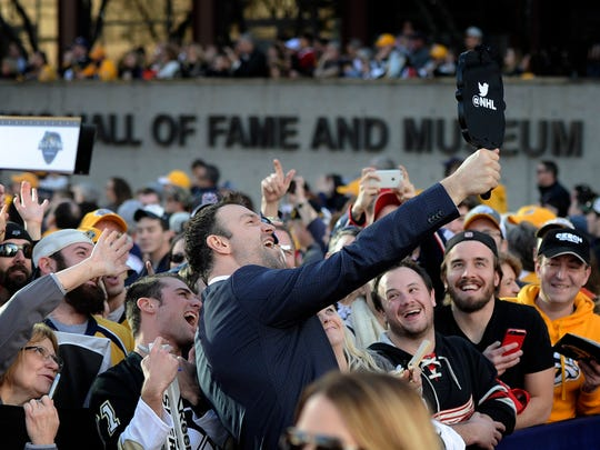 NHL All-Star John Scott poses with fans on the red