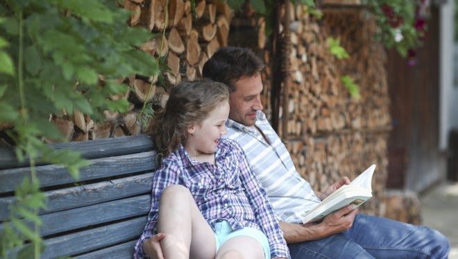Father sharing boy with girl on bench