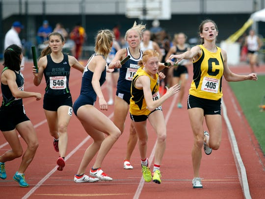 Corning's Claire Mason takes the baton from Lindsey Butler in heat 2 of the Girls 4x800 meter relay at the NYSPHSAA Outdoor Track & Field Championships at Cicero-North Syracuse High School. The Corning boys and girls each finished third in the event.