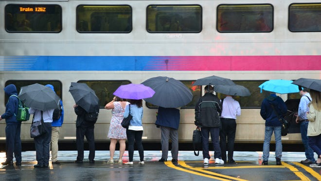 Commuters use umbrellas to shield themselves from the rain as they wait to board an NJ Transit Train on Fair Lawn Ave in Fair Lawn on Thursday morning June 28, 2018.