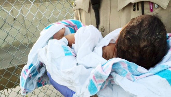 This Friday, Nov. 27, 2015 photo provided by the Los Angeles County Sheriff's Department shows an unidentified deputy holding an infant girl where she was found abandoned under asphalt and rubble, lower left, near a bike path in Compton, Calif.