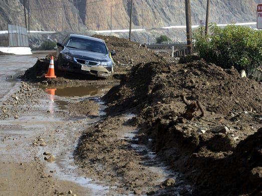 A car is trapped in a mud slides that closed a 10 mile