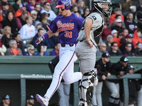 Clemson freshman Bryce Teodosio(31) scores by South Carolina junior Hunter Taylor during the bottom of the seventh inning on Saturday at Fluor Field in Greenville.