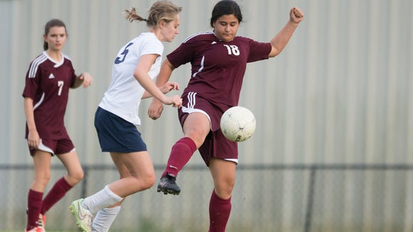 LAMP's Maria Paolini (18) clears the ball as St. James' Tessa Evans pressures her during the Class 4A/5A playoff match on Friday, April 24, 2015, at St. James in Montgomery, Ala.