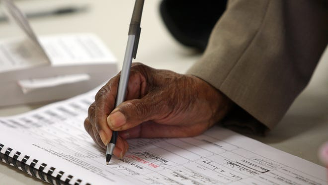 Merl Scott signs in prior to voting on Tuesday at the Holmes Marshall Fire Company in Piscataway.