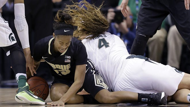 Purdue Boilermakers guard April Wilson (25) grabs a loose ball from Michigan State Spartans center Jasmine Hines (4) in the first half of their Big Ten Women's Basketball Tournament game Friday, Mar 4, 2016, at Bankers Life Fieldhouse in Indianapolis.