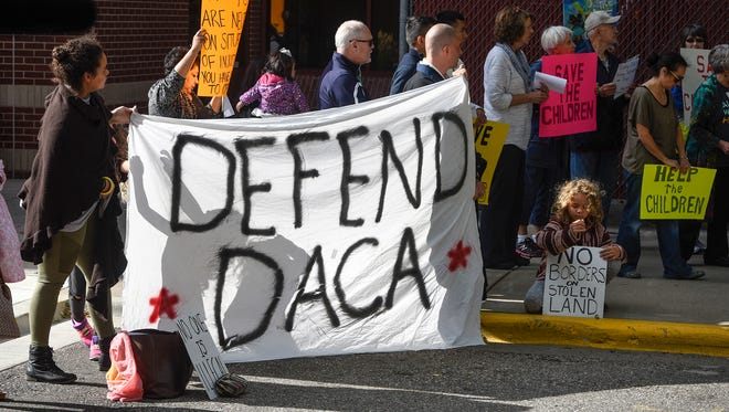 People hold signs near the Stearns County Courthouse Tuesday, Sept. 5, in St. Cloud during a rally in support of the Deferred Action for Children Arrivals program.