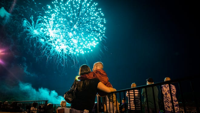 Attendees watch a fireworks show from the Fallen Heroes Memorial Bridge in downtown Muncie on the Fourth of July.
