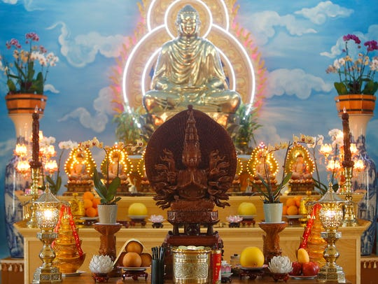 Statues of the Buddha and, in the center, a wood-carved