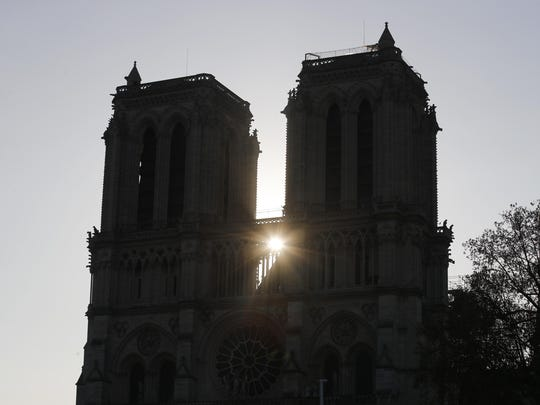 The sun rises between the two towers of Notre Dame cathedral Wednesday, April 17, 2019, in Paris. Nearly $1 billion has already poured in from around the world to restore Notre Dame Cathedral in Paris after a massive fire.