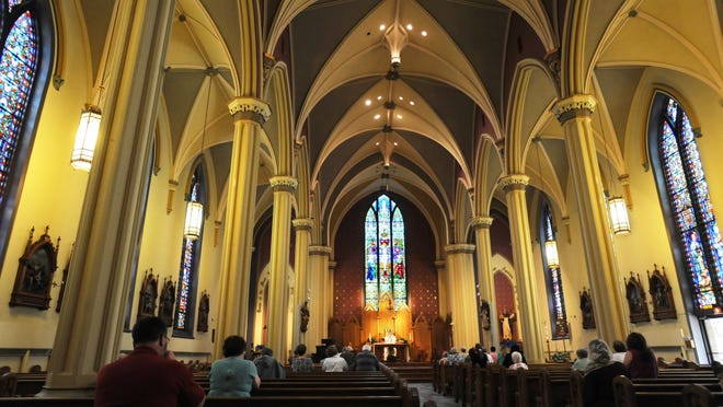 Father Stephen Dominic Hayes leads a noon Mass at St. Thomas Aquinas Catholic Church in downtown Zanesville. Many downtown churches face an aging congregation and few new members.