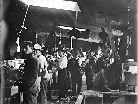 Men work inside a button factory. Lansing and Muscatine