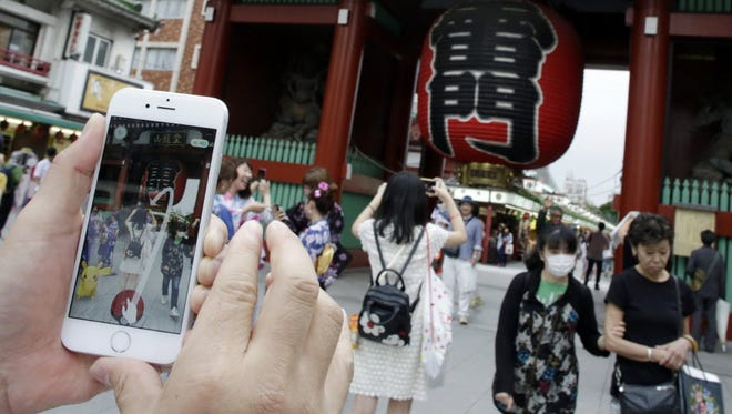 "A man tries to catch a Pikachu, a Pokemon character, while he plays ""Pokemon Go"" in front of Kaminarimon, or Thunder Gate, at the Sensoji temple in Tokyo's Asakusa shopping and tourist district, on July 22."