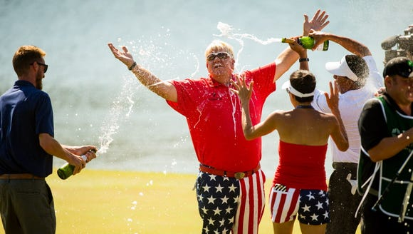 John Daly celebrates on the 18th green following his