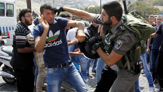 In this Oct. 2, 2015, file photo, an Israeli border policeman exchanges blows with a Palestinian man during a confrontation after Friday prayers outside the Old City in Jerusalem.